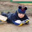 Stock Photo: Toddler lies with shovel