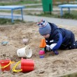 Stock Photo: Toddler playing in sandbox