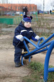 Toddler holding handle of seesaw — Stock Photo