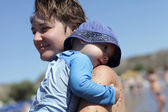 Mother holding her toddler on a beach — Stock Photo