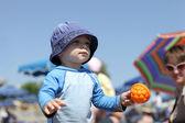 Toddler with toy on a beach — ストック写真