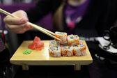 Girl takes sushi — Stock Photo