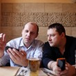 Stock Photo: Two men using mobile phones