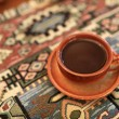 Cup of coffee on a tablecloth — Stock Photo