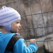 Toddler looking through fence — Stock Photo