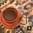 Brown cup of coffee on a tablecloth — Stock Photo