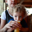 Toddler drinking juice — Stock Photo