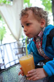 Toddler drinks juice — Stock Photo