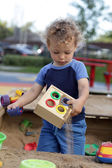 Curly child at sand box — Stock Photo