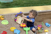 Curly boy at sand box — Stock Photo