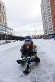Boy slides on snow scooter — Zdjęcie stockowe