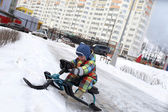 Toddler on a snow scooter — Стоковое фото
