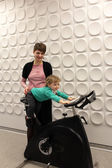 Family at exercise bicycle — Stock Photo