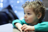 Pensive kid at table — Stock Photo