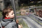Boy looking at toy city — Stock Photo