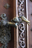 Door handle with a pigeon pecking a head — Stock Photo