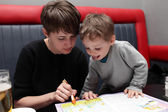Mother and son with coloring book — Stock Photo