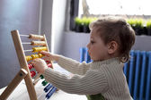 Child playing with abacus — Stock Photo