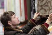 Woman choosing curtains — 图库照片