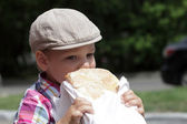 Child eating loaf of bread — Stock Photo