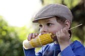 Hungry boy eating corn — Stock Photo