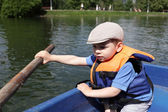 Boy rowing boat — Stock Photo