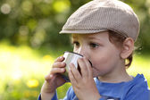 Kid drinking tea outdoor — Stock Photo