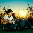 Love story. A young man playing guitar for his girl. — Photo