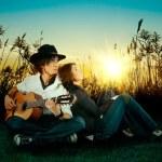 milostný příběh. mladý muž, který hrál na kytaru za jeho dívka — Stock fotografie