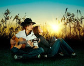 Love story. A young man playing guitar for his girl. — Stock Photo