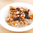 Stock Photo: Oatmeal with raisins, nuts and maple syrup