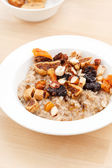 Oatmeal with raisins, nuts and maple syrup — Stock Photo