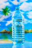 Bottle of water on the beach — Stock Photo