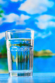 Glass of the water on the beach — Stock Photo