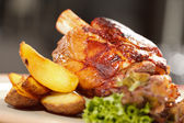 Roasted pork knuckle with potatoes — Stock Photo