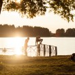 Silhouette of kids jumping from river dock — Stock Photo