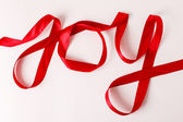 Joy word written in red ribbon — Zdjęcie stockowe