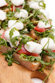 Tomato, mozzarella and arugula sandwich — Stock Photo