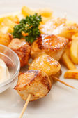Chicken skewers with french fries — Stock Photo