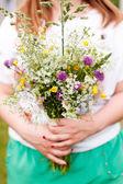 Woman holding wild flowers — Zdjęcie stockowe