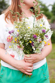 Woman holding wild flowers — Stock Photo