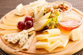 Cheese plate with grapes — Stock Photo
