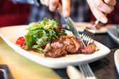 Man eating meat with salad — Stock Photo
