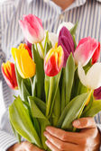 Bouquet of tulips in a hand — Stock Photo