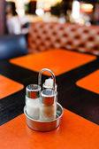 Pepper and salt shaker on table — Stockfoto