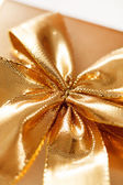 Present with gold bow — Stock Photo