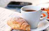 Continental breakfast with coffee and croissant — Stock Photo