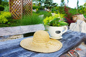 Hat and flowers on garden table — Stock Photo