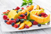 Different fruits and berries on a white plate — Stock Photo
