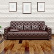 Leather sofa near the wall — Stock Photo